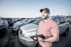 Dealer on Car Lot Using iPad to Manage Floor Plan Line of Credit