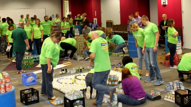 CANStruction volunteers in green matching shirts work together to build structures out of canned goods