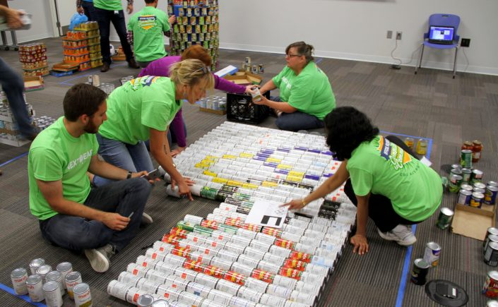 CANstruction volunteers work together to build Olympic rings out of canned goods