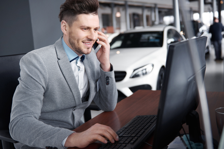 dealer using the computer while on the phone