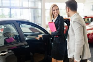 Car dealership sales person showing a customer a vehicle