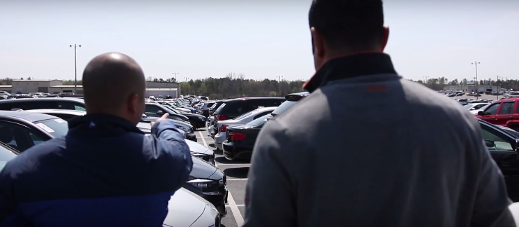 man on car lot pointing out cars that used floor plan financing for used car dealers