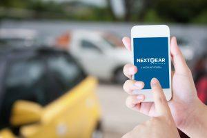 dealer on car lot using NextGear Capital's account portal on their phone as their auto floor plan lending solution