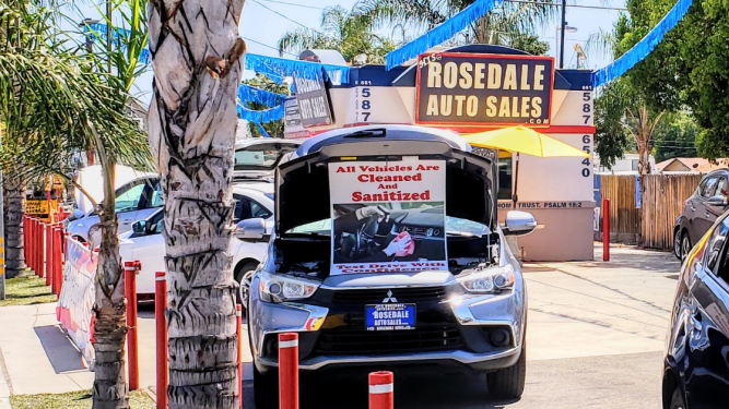 A car with a sign that says it has been sanitized
